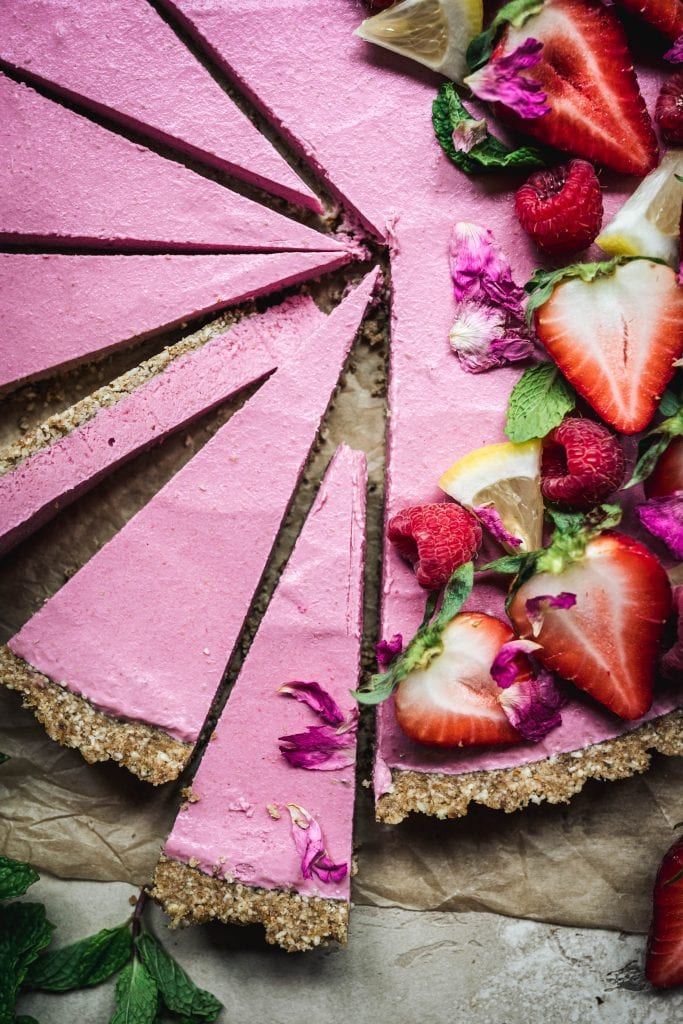 Close up Overhead view of vegan strawberry mousse tart garnished with fresh berries and sliced thinly on parchment paper