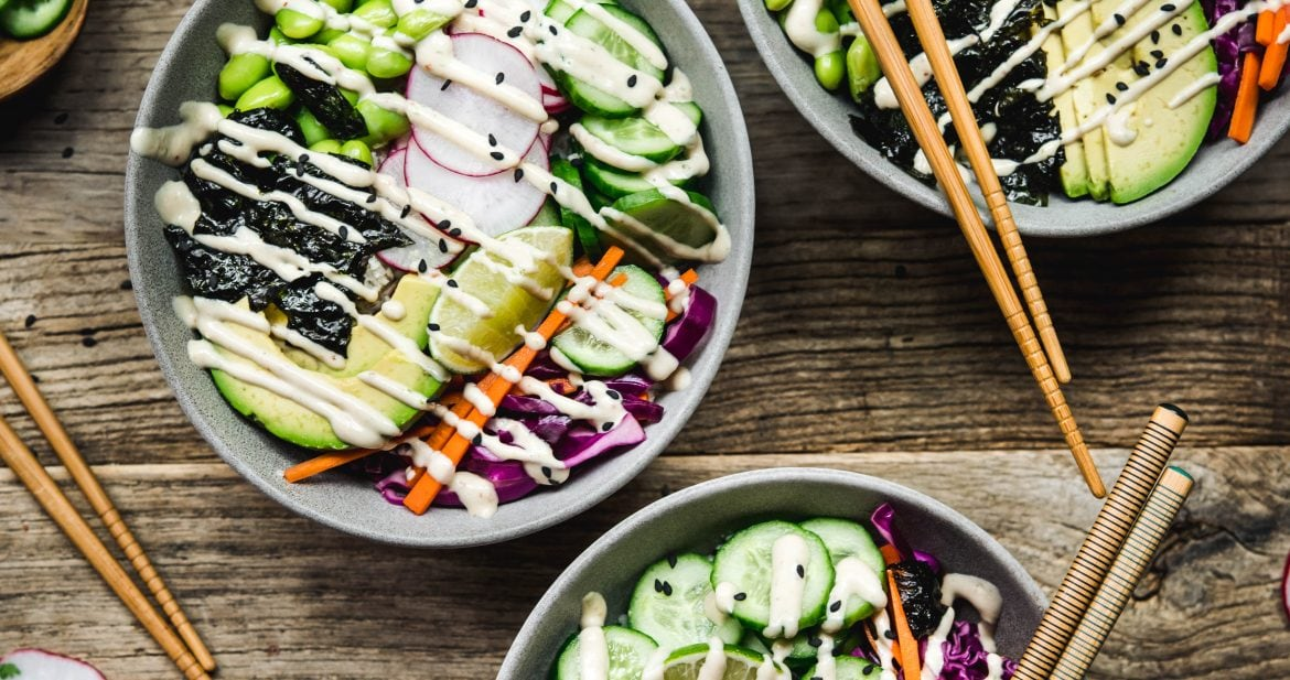 Overhead view of vegan sushi bowls with cucumber and miso tahini dressing on a wood table with chopsticks