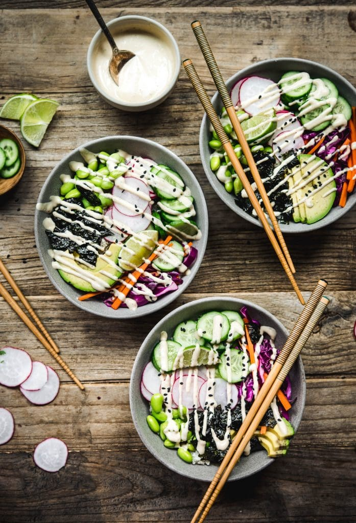 Overhead view of vegan sushi bowls with miso tahini dressing on a wood table with chopsticks