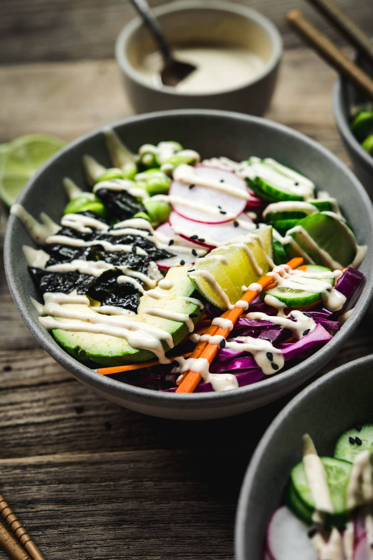 Close up side view of vegan sushi bowls with miso tahini dressing on a wood table with chopsticks