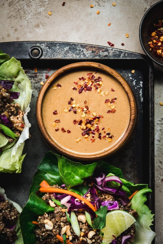 Overhead view of vegan spicy peanut sauce in wood bowl on antique tray to top vegan asian lettuce wraps