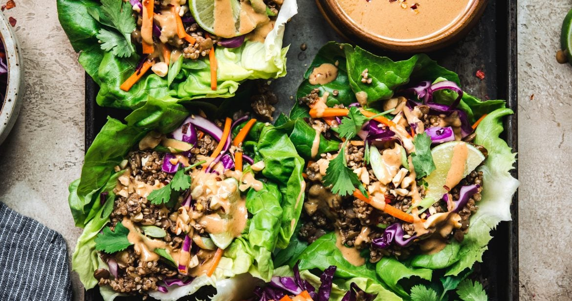 Overhead view of vegan asian lettuce wraps with lentil walnut filling and peanut sauce on antique tray