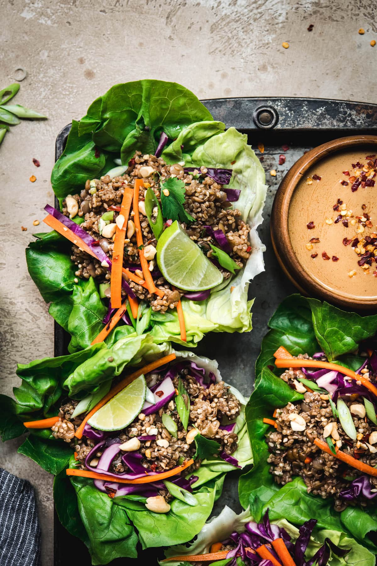 Close up Overhead view of vegan asian lettuce wraps with lentil walnut filling and peanut sauce on antique tray