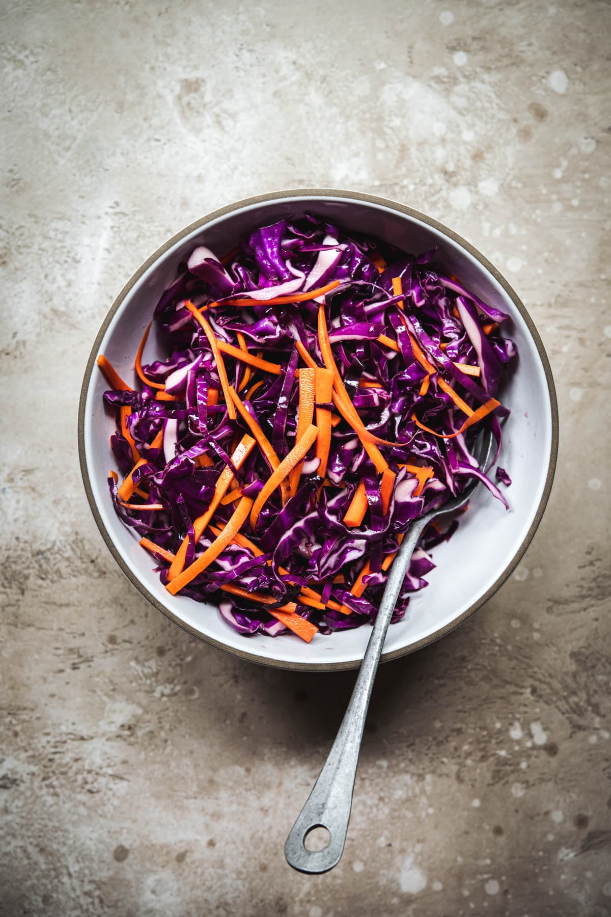 Overhead view of marinated purple cabbage and carrots in a white bowl to top asian lettuce wraps