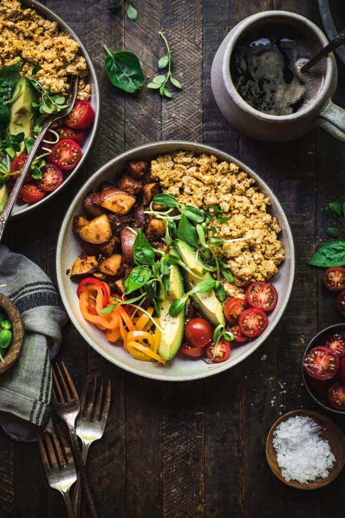 Overhead of two vegan breakfast bowls with spicy potatoes and tofu scramble