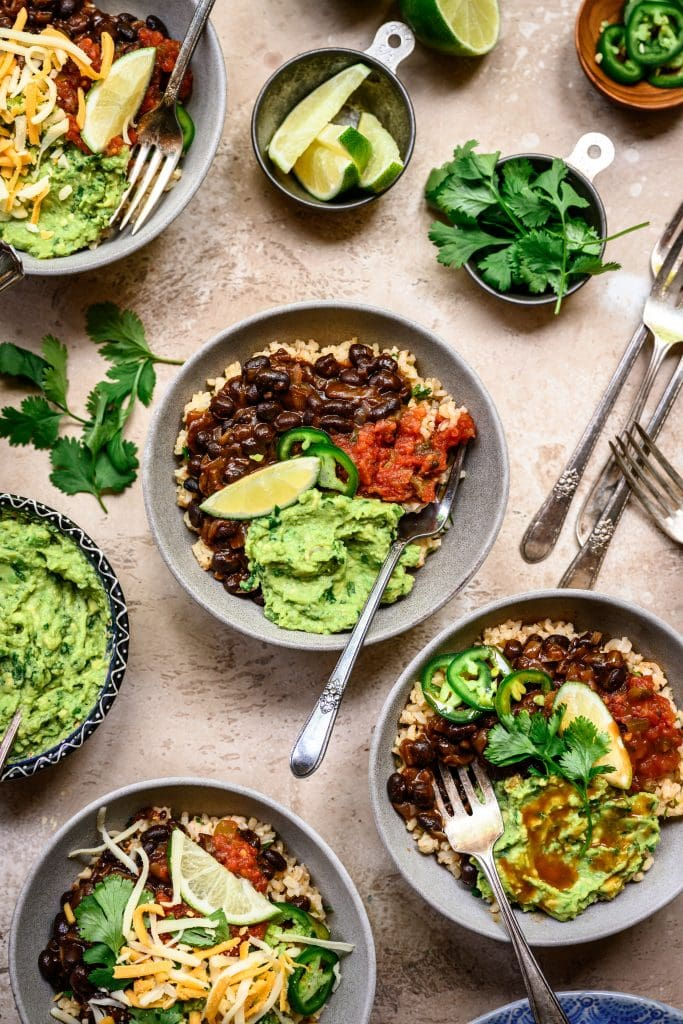 Overhead view of vegan burrito bowls with spicy black beans and guacamole in grey bowls on rustic background