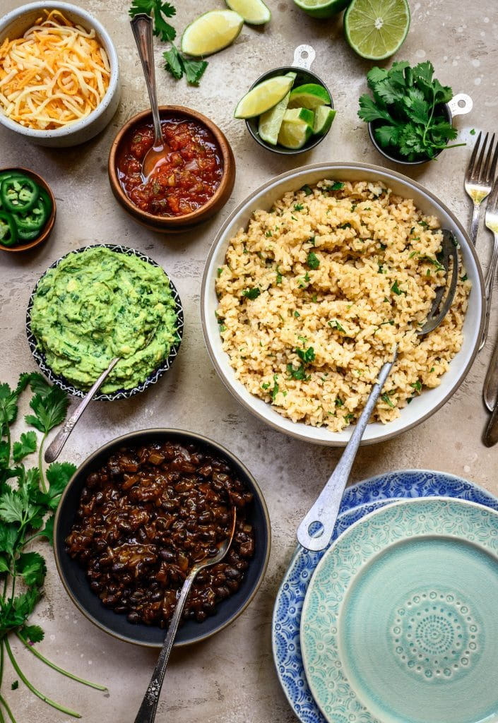 Overhead view of vegan burrito bowl fillings in various sized bowls on rustic background