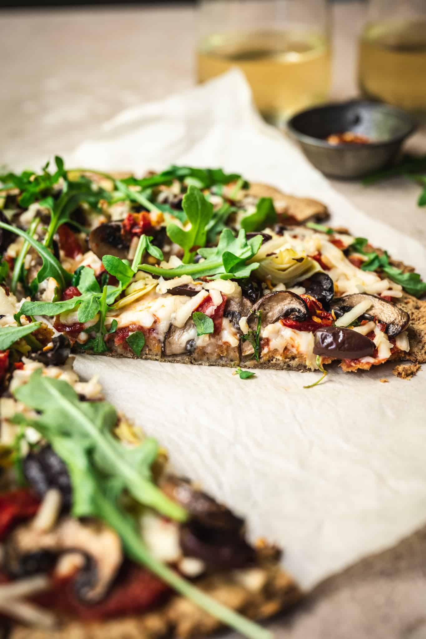 Side view of slice of vegan cauliflower crust pizza