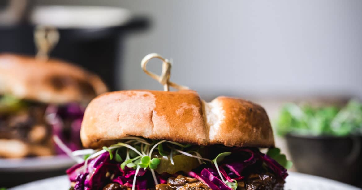 Side view of pulled mushroom sandwich with purple cabbage on a white plate