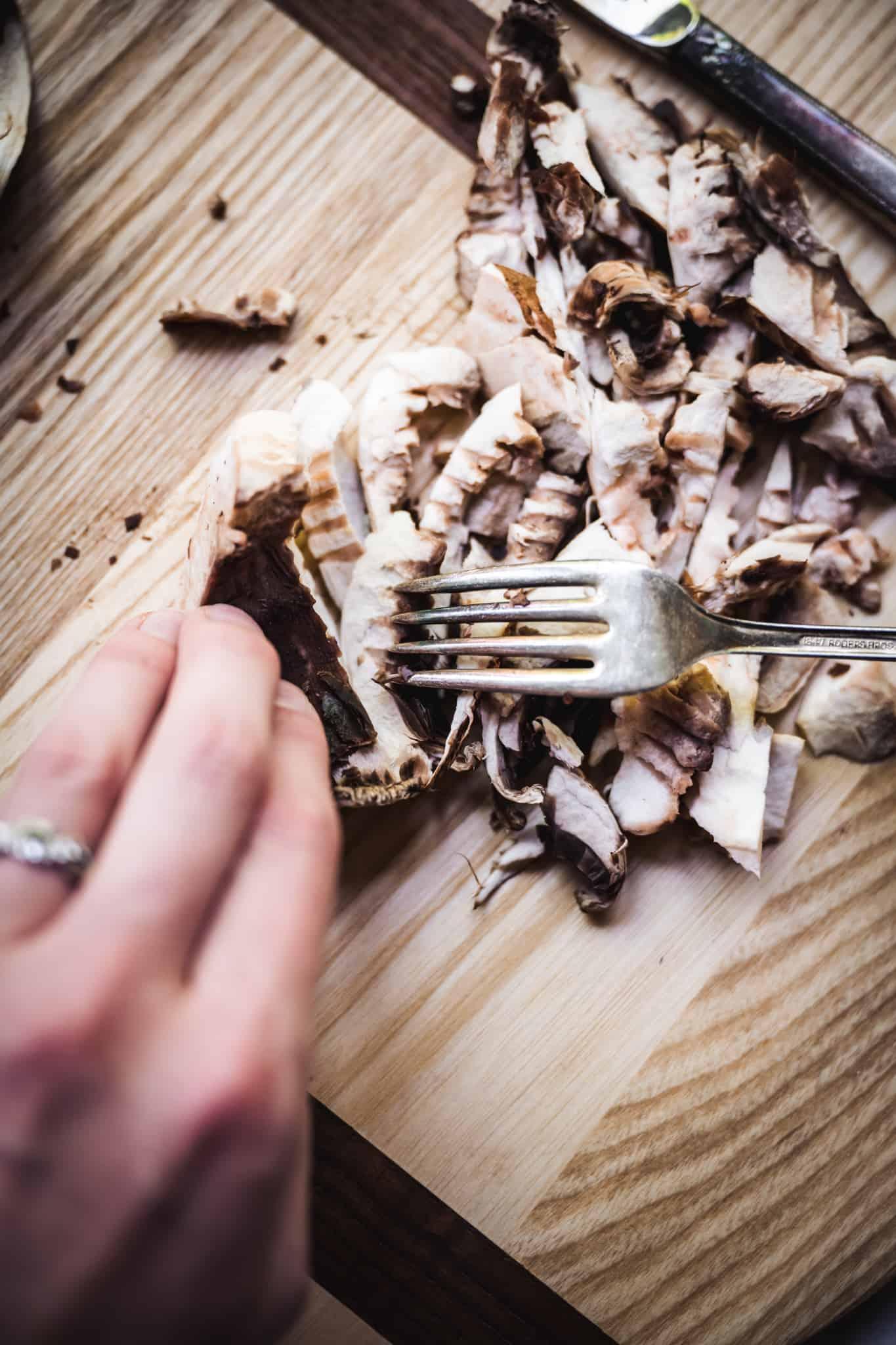 Person shredding portobello mushrooms