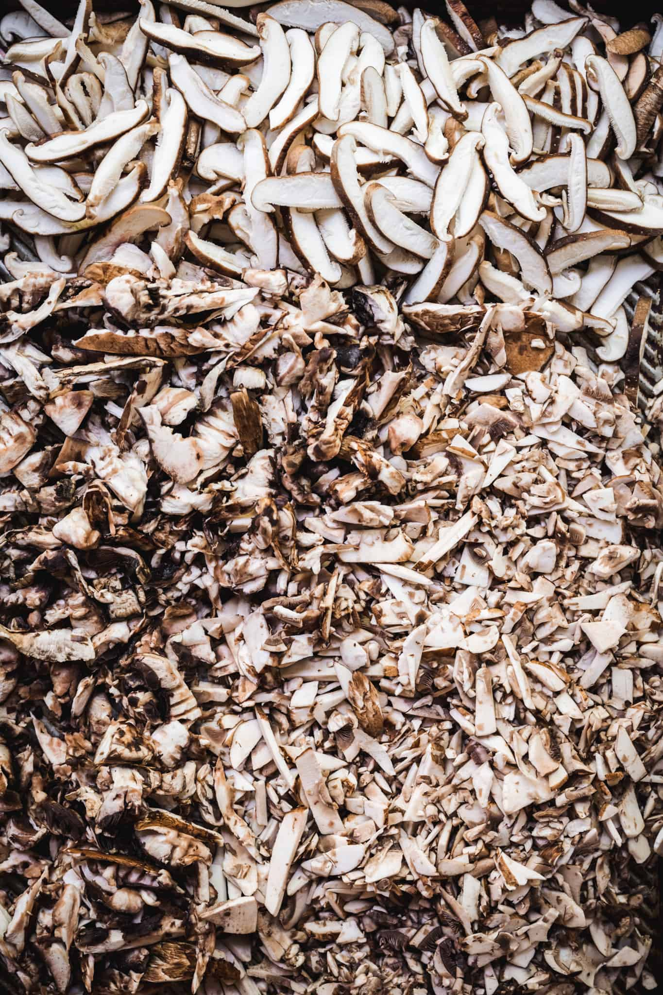 Overhead view of sliced mushrooms on a sheet pan