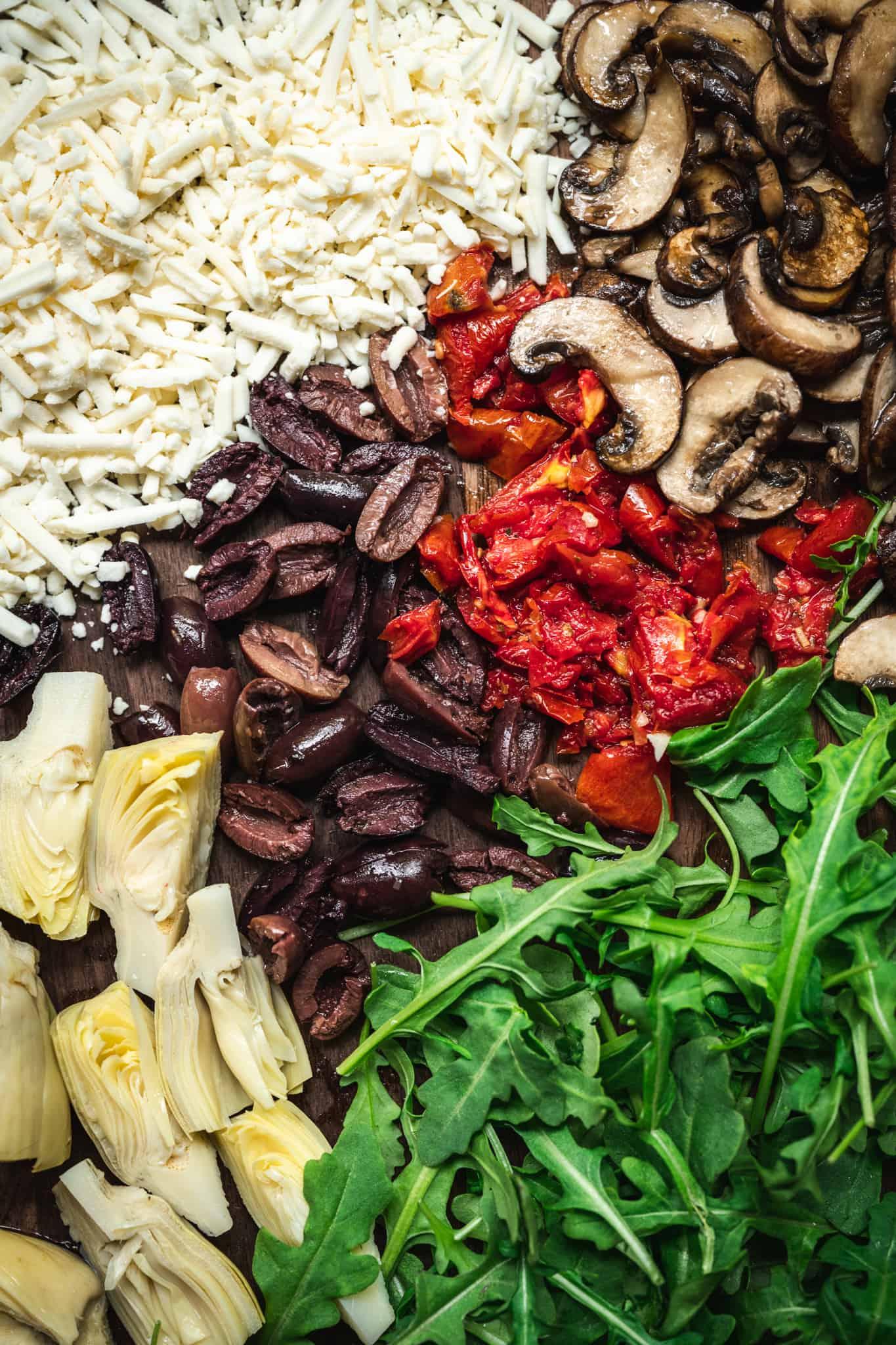 Overhead of vegan cheese, mushrooms, olives, sun-dried tomatoes, artichokes and arugula