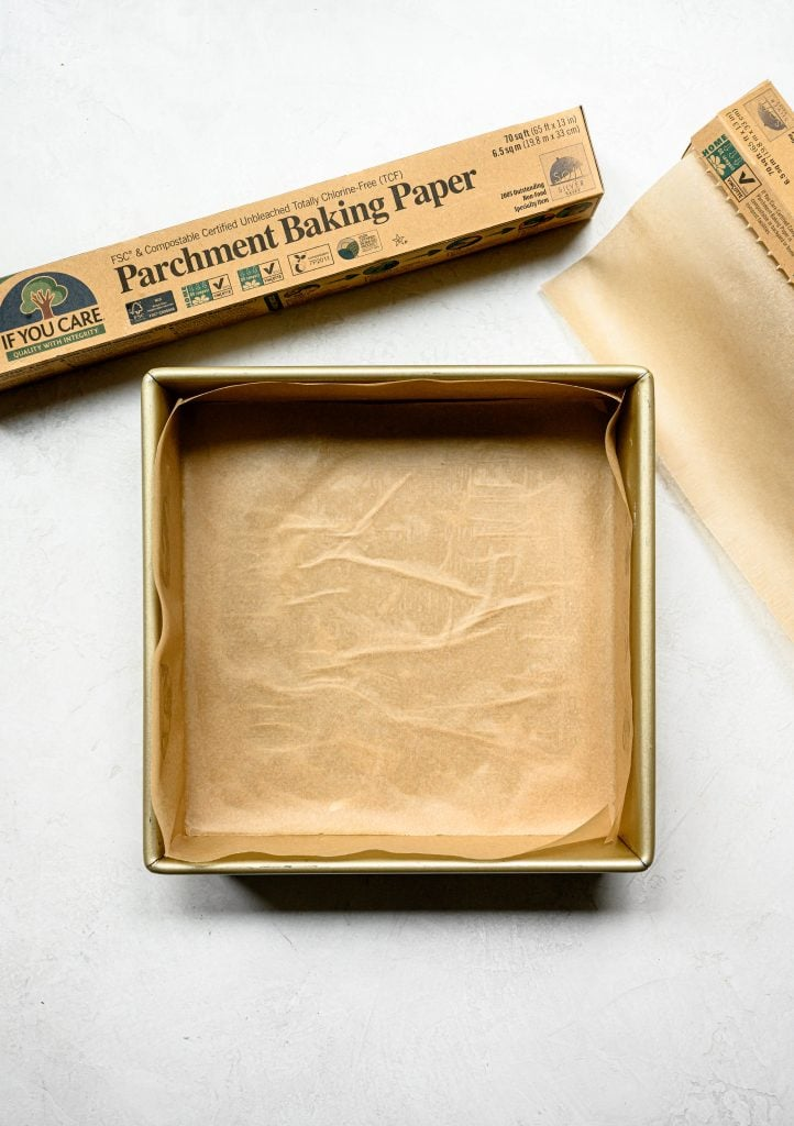 Overhead view of parchment paper in square brownie pan on white background