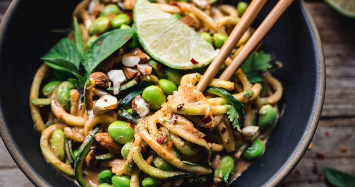 overhead of red curry almond butter zucchini noodles with chopsticks