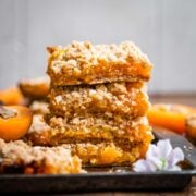 4 stacked apricot crumble bars on a tray.