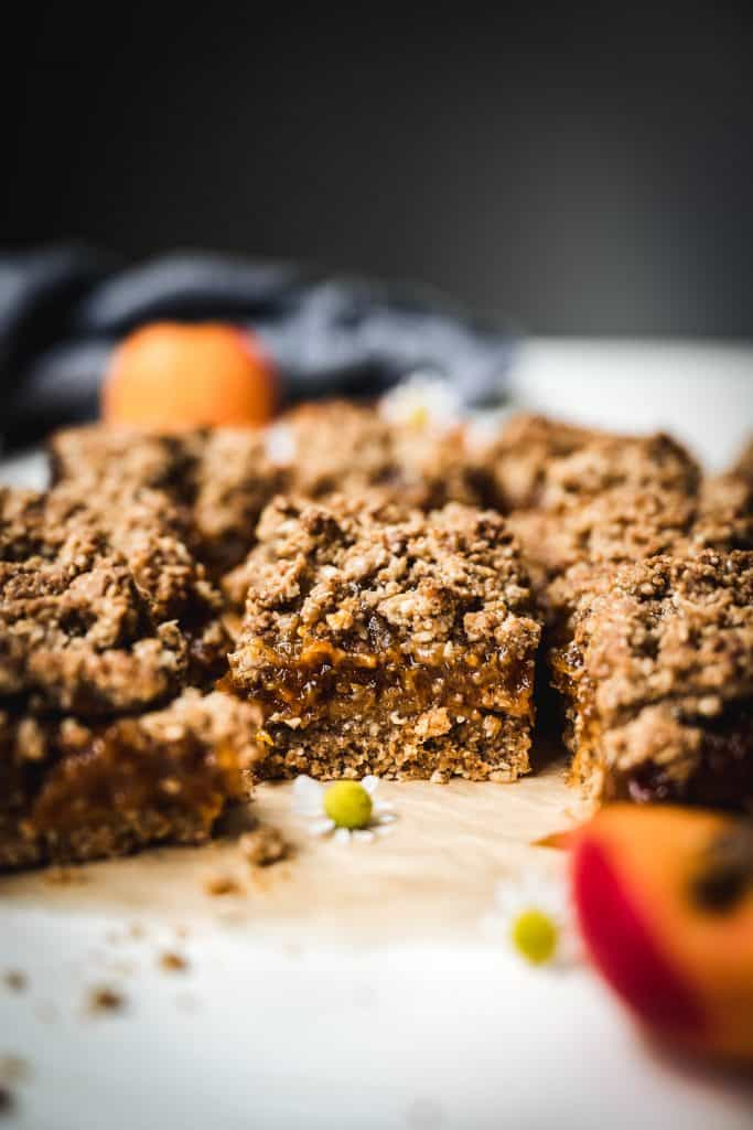 side view of apricot oat bars on parchment paper with fresh apricots in background