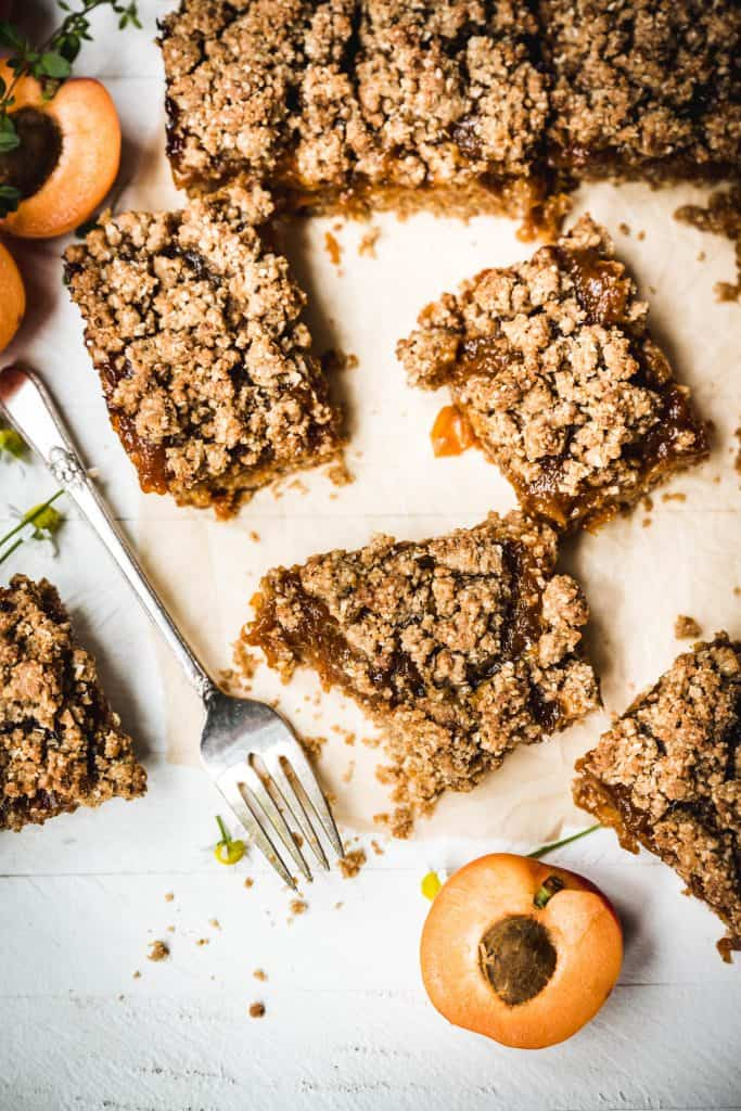 Overhead view of sliced vegan apricot oat bars on parchment paper