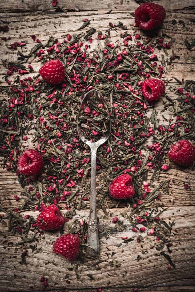 Overhead view of loose leaf raspberry green tea on a wood table