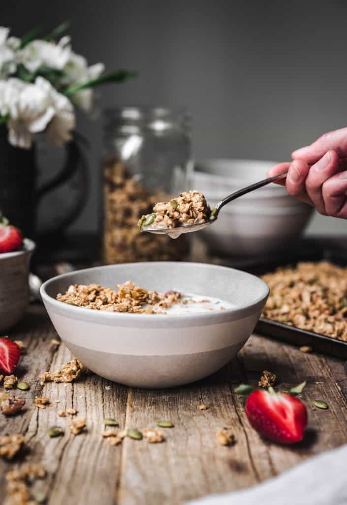 Person holding spoon of granola over bowl
