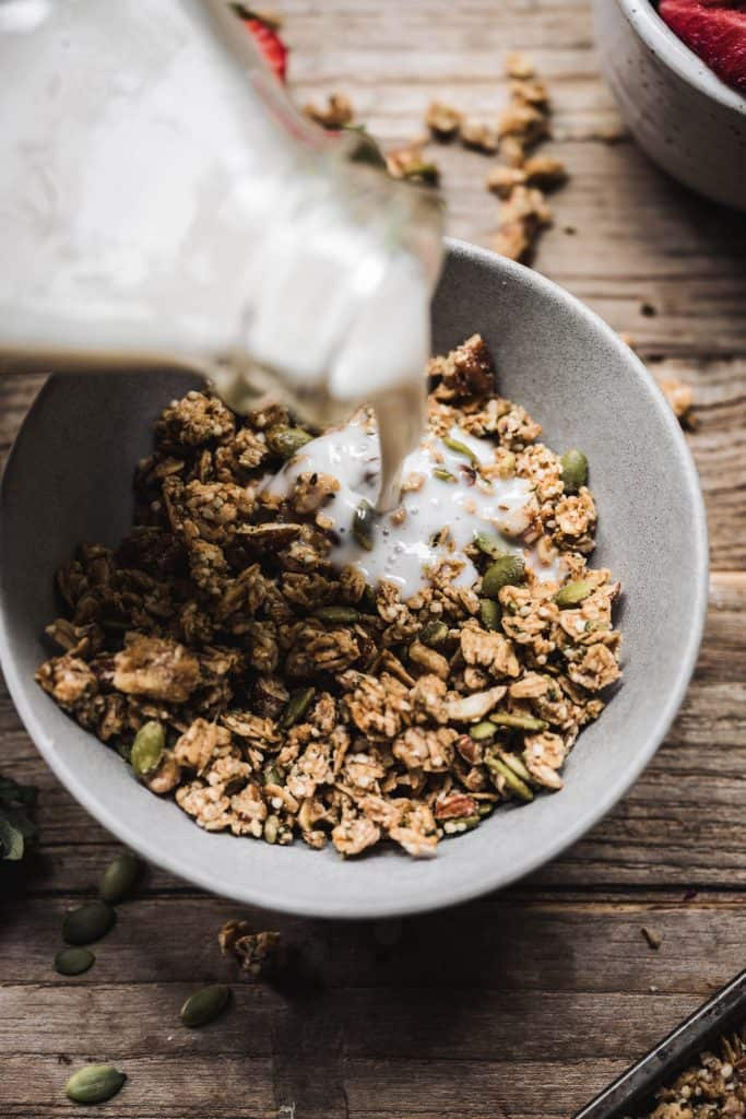 Close up of pouring milk into a bowl of homemade granola