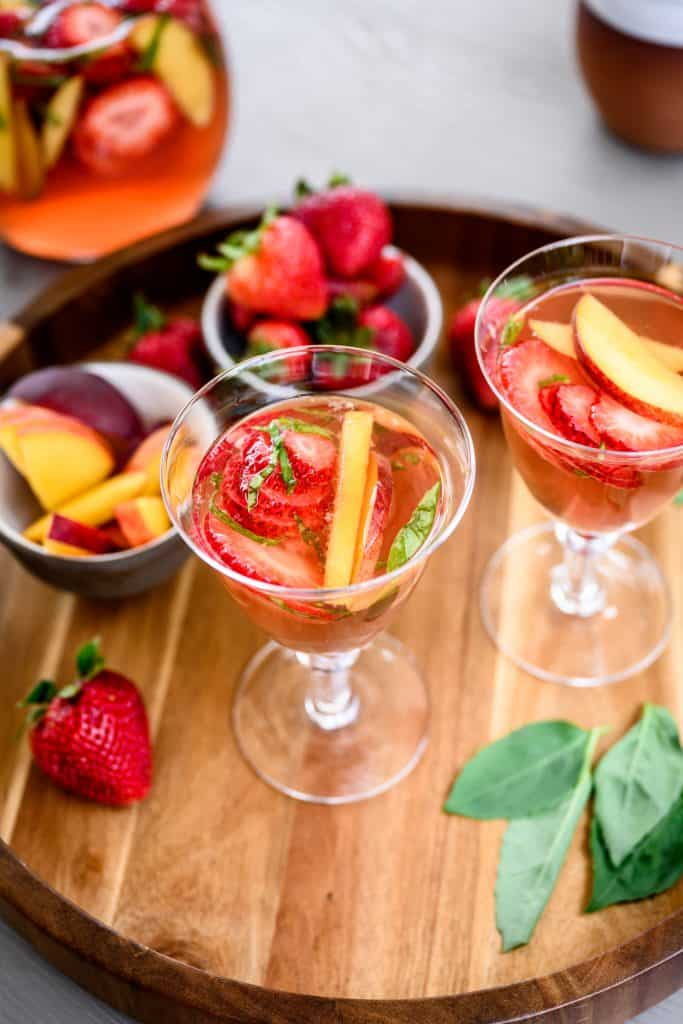 Side view of strawberry peach sangria in a cocktail glass on wood tray