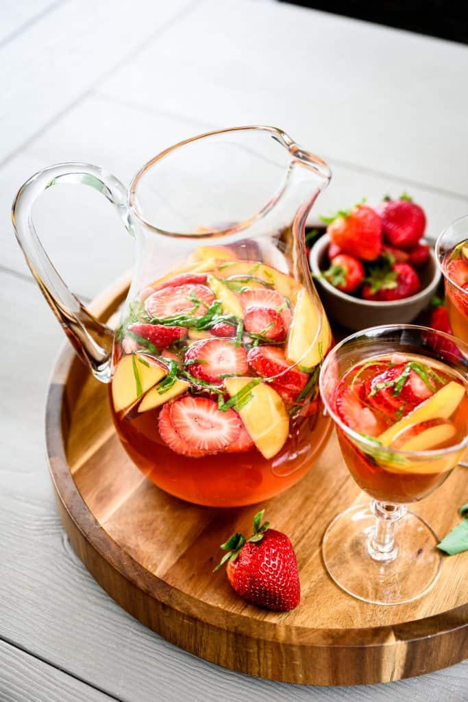 Side view of strawberry peach basil sangria in a large pitcher on wood tray