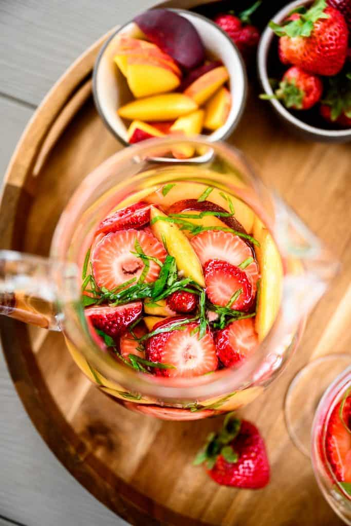 close up overhead of strawberry peach basil white wine sangria in a large pitcher