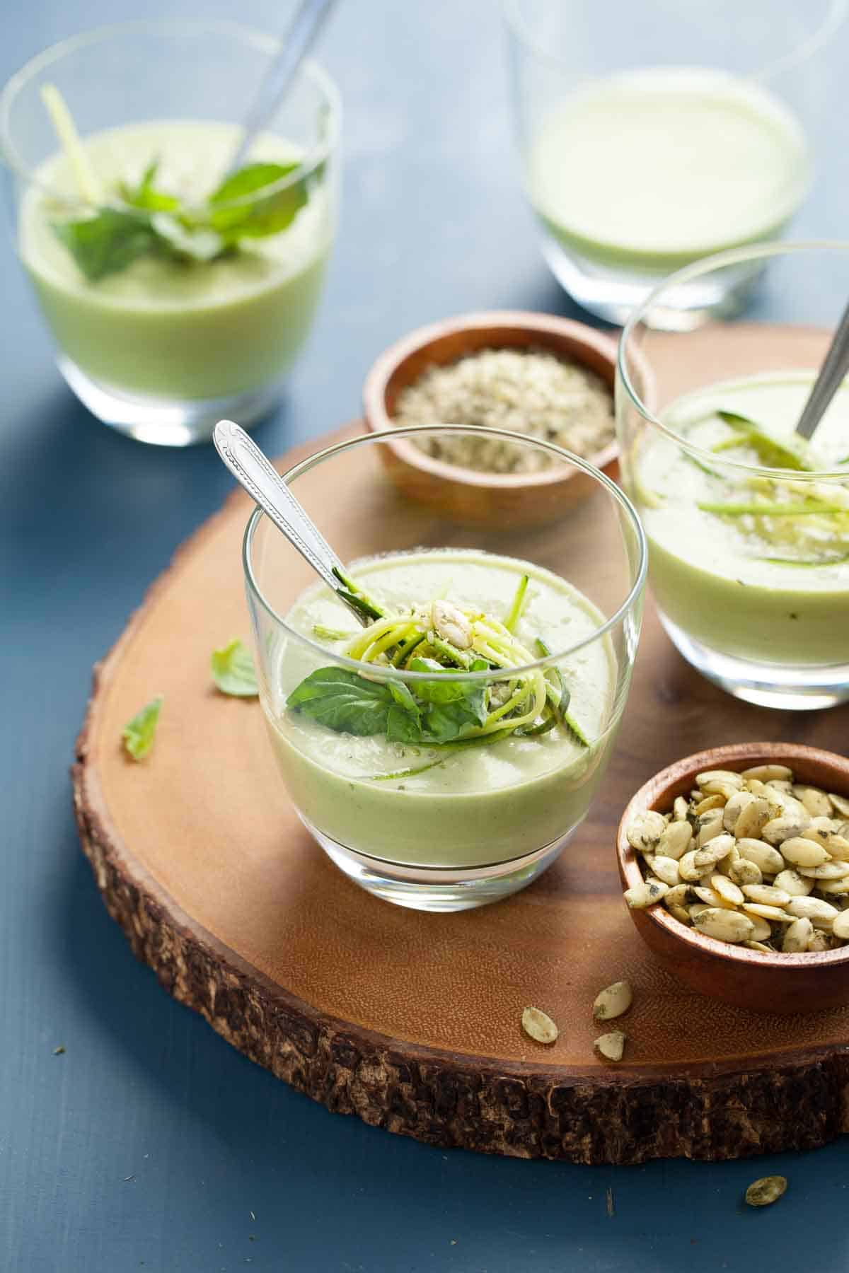 Chilled vegan zucchini basil soup in a small glass on a wooden board