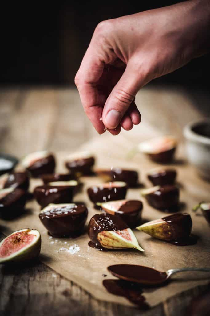 Person sprinkling flaky salt on chocolate dipped figs