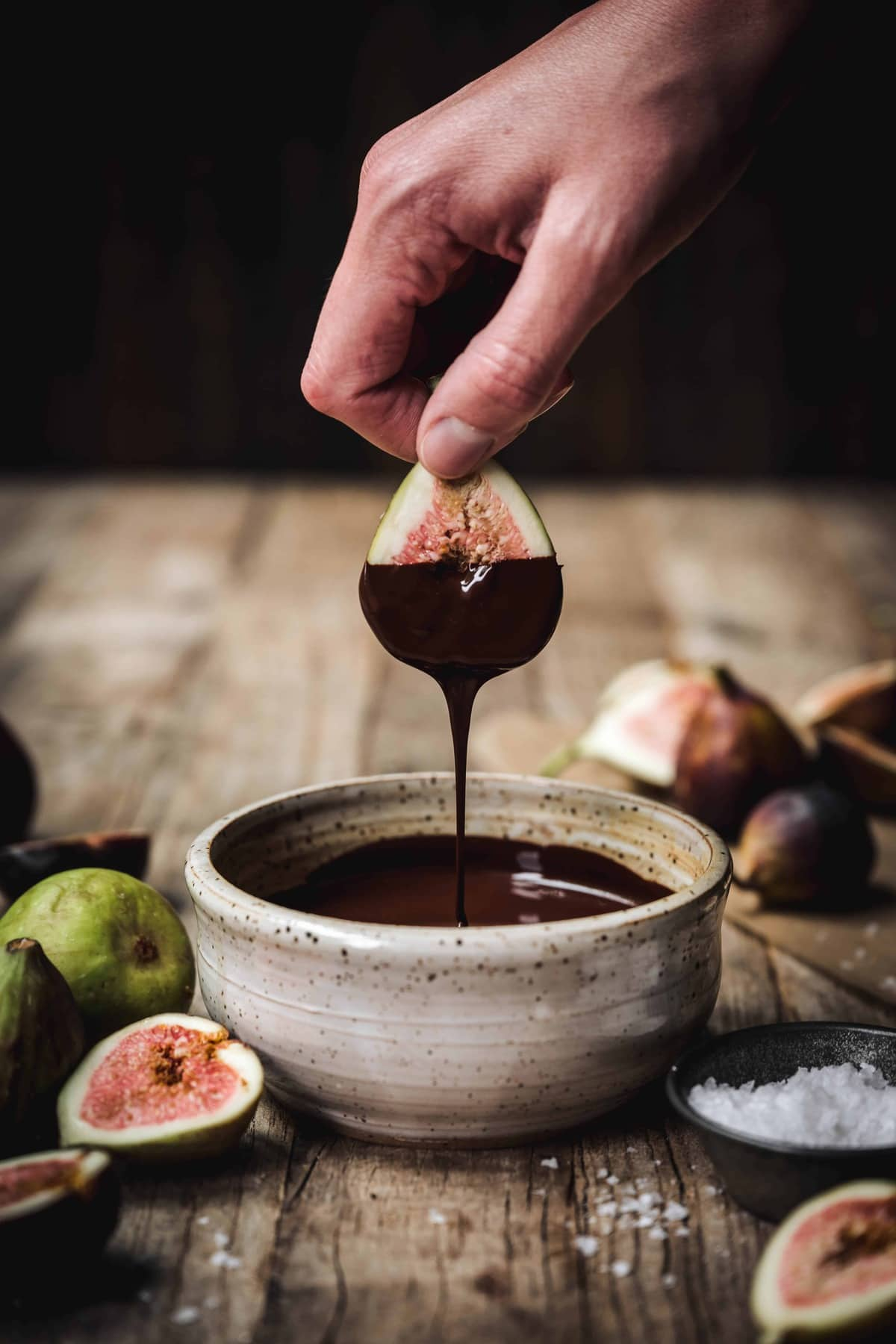 person dipping fresh fig in melted dark chocolate