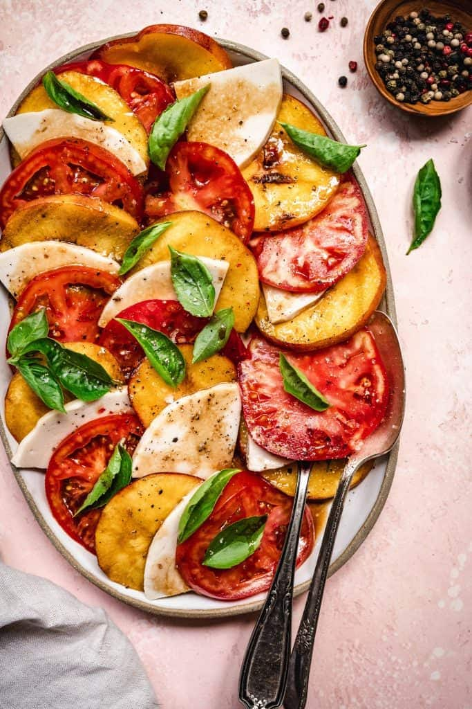 overhead of grilled peach caprese salad with vegan cheese and balsamic dressing