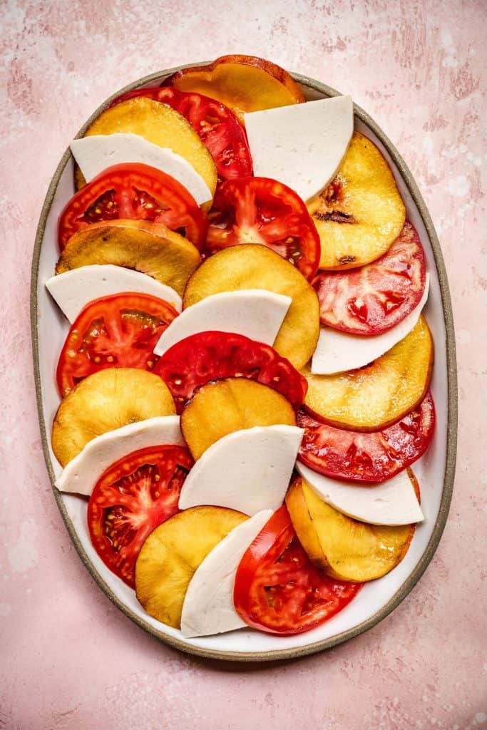 overhead of perfectly layered vegan caprese salad with grilled peaches and tomatoes