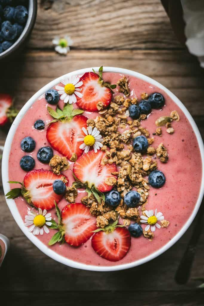 Close up overhead of strawberry smoothie bowl with fresh berries and granola