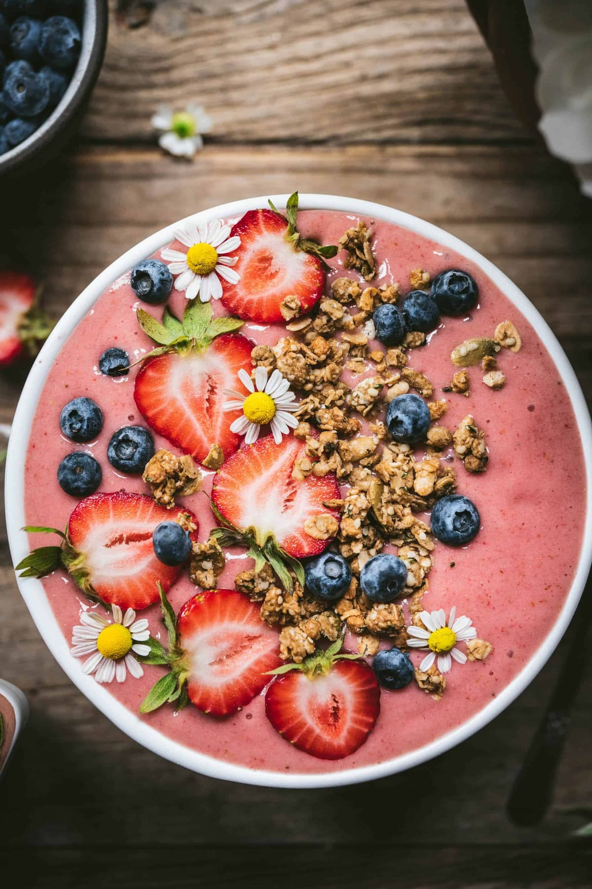 overhead view of vegan strawberries and cream smoothie bowl topped with fresh fruit and granola