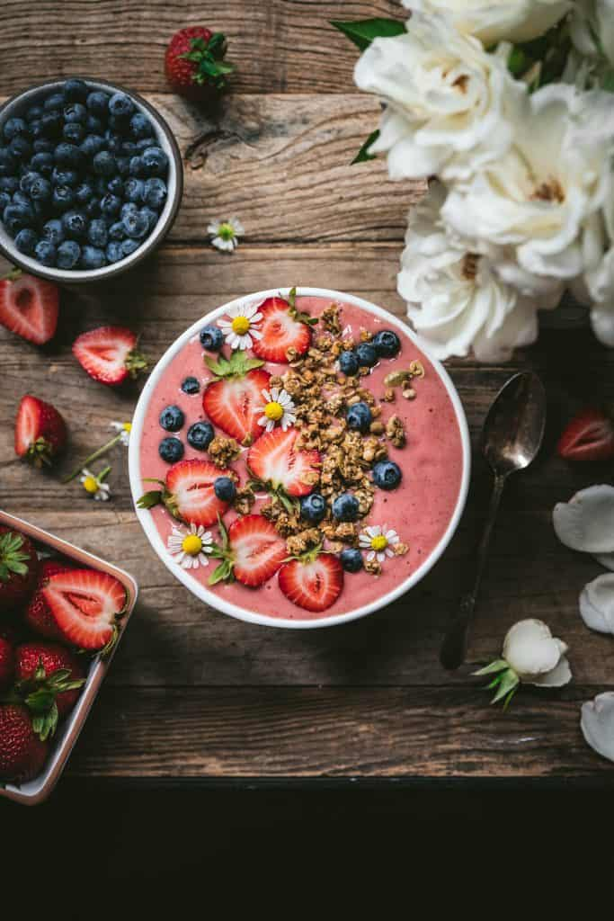 Overhead view of beautiful strawberries and cream smoothie bowl with fresh berries and granola on wood table