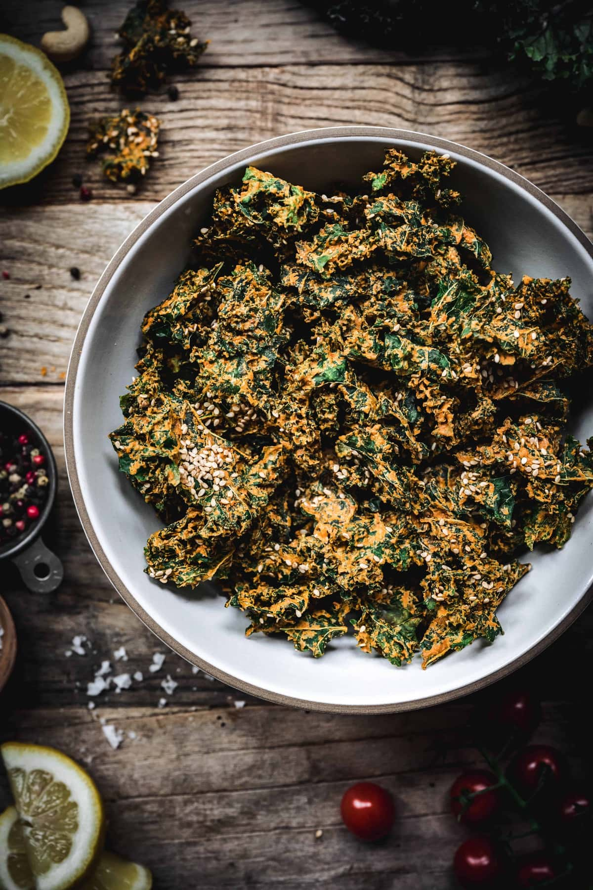 Close up of cheesy vegan kale chips in a white bowl on wood table