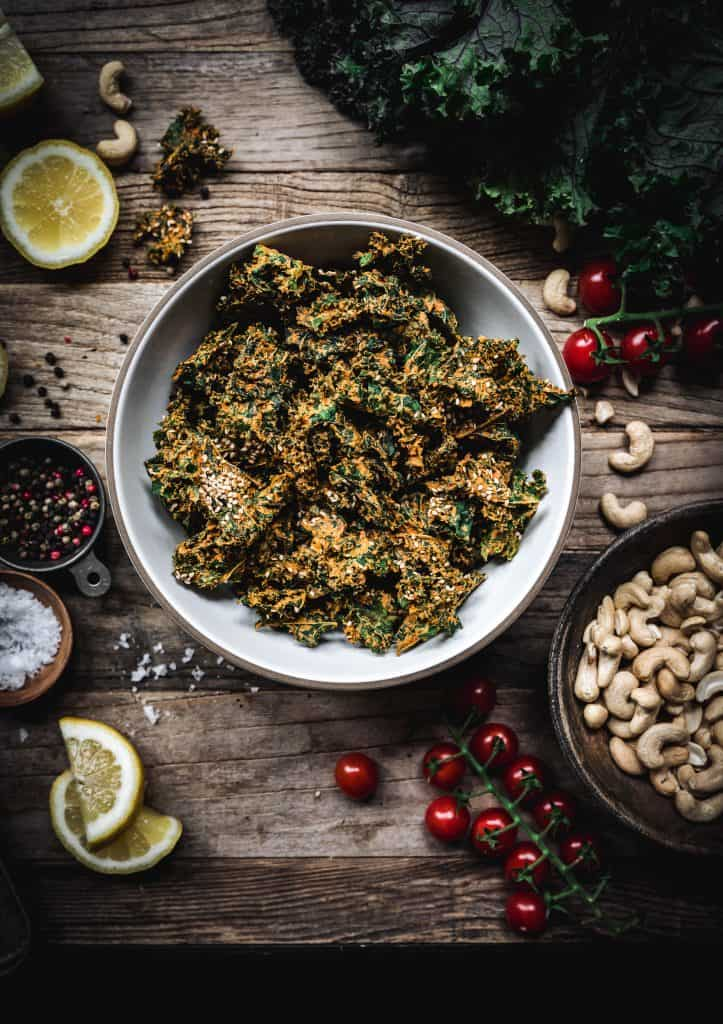 Overhead view of bowl of cheesy vegan kale chips on a wood table with ingredients around bowl