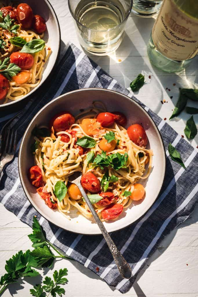 Overhead view of simple burst cherry tomato pasta in a bowl in direct sunlight with glass of white wine