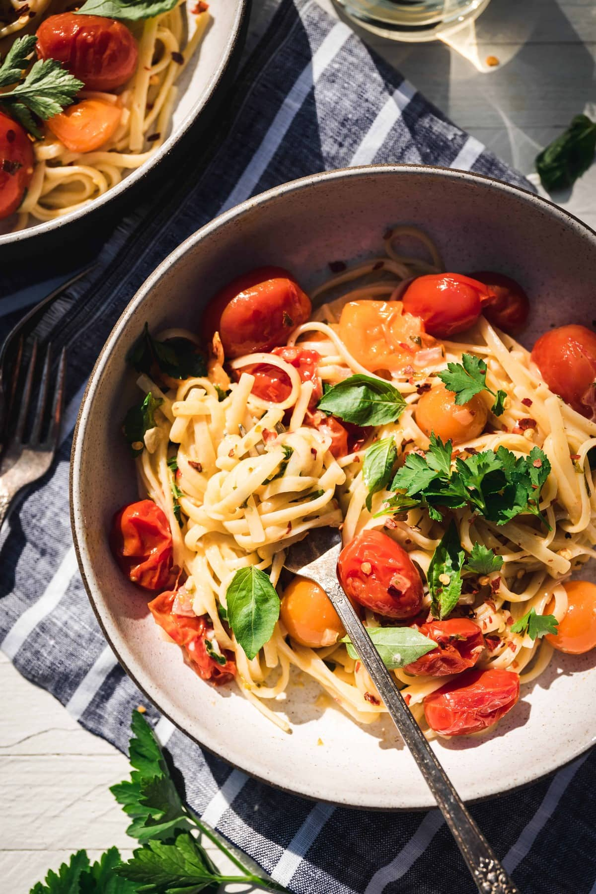 Close up Overhead view of simple burst cherry tomato pasta in a bowl in direct sunlight with glass of white wine