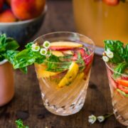 Glass of strawberry peach sangria garnished with fruit.