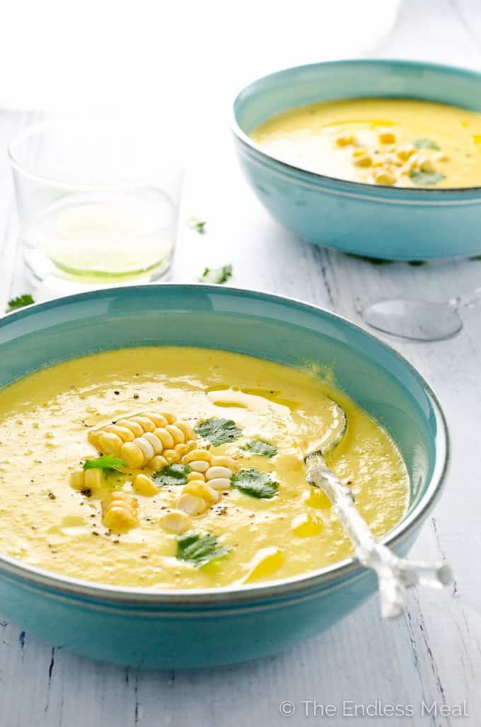 45 degree angle of vegan sweet corn gazpacho in a blue bowl