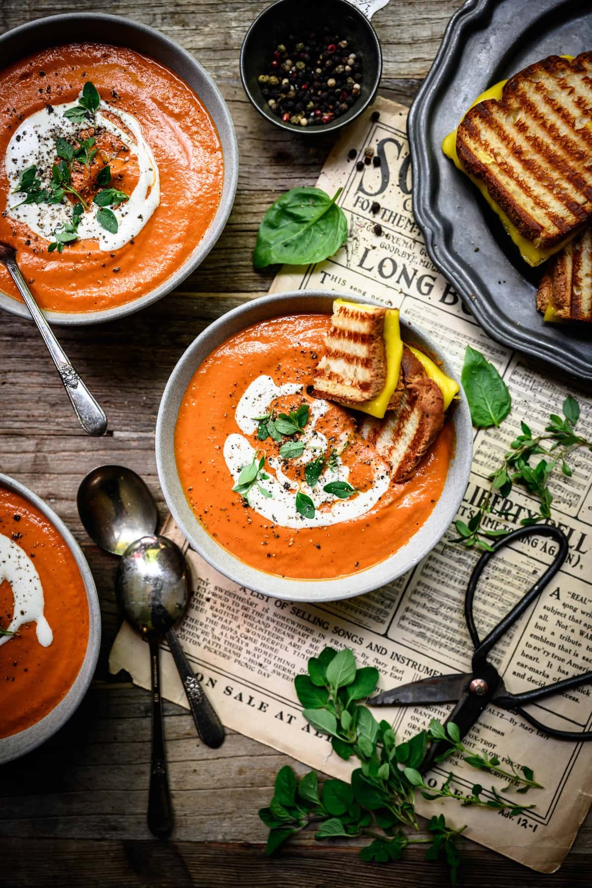 overhead of three bowls of creamy vegan tomato soup with vegan grilled cheese