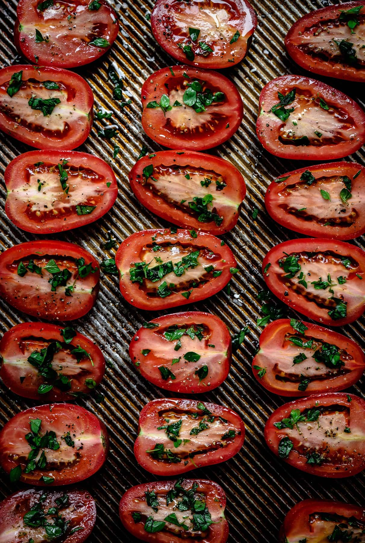 overhead of halved roma tomatoes on a baking sheet before roasting