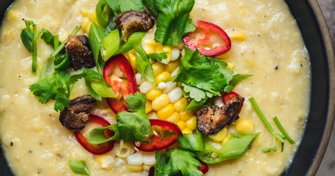 overhead of a bowl of creamy vegan coconut corn chowder topped with crispy dates