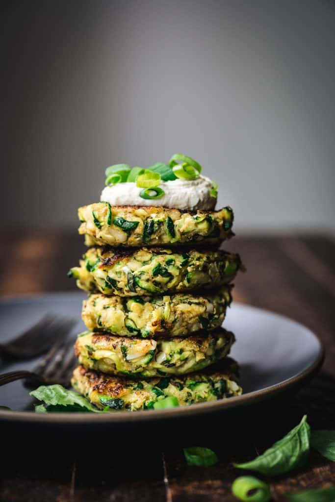 side view of a stack of gluten free zucchini fritters with vegan lemon cashew cream on top