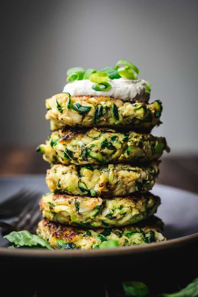 side view of a stack of gluten free zucchini fritters with lemon cashew cream and scallions