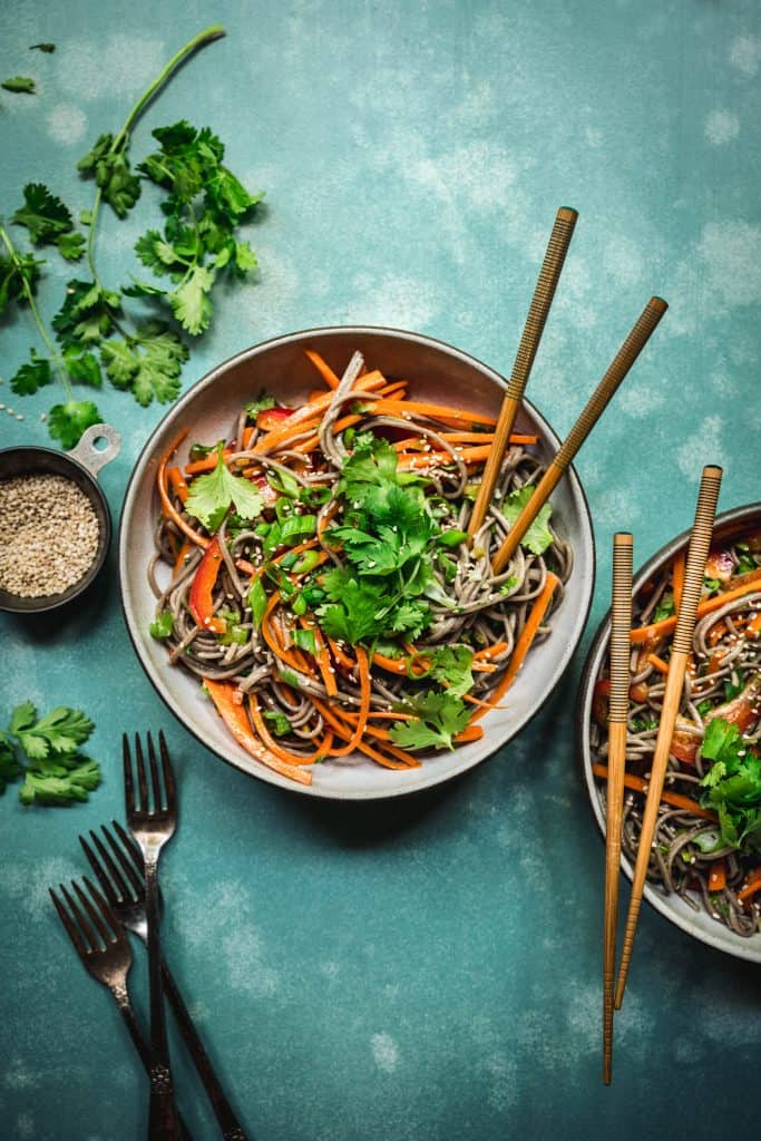 overhead of soba noodle salad with citrus scallion dressing on a teal background