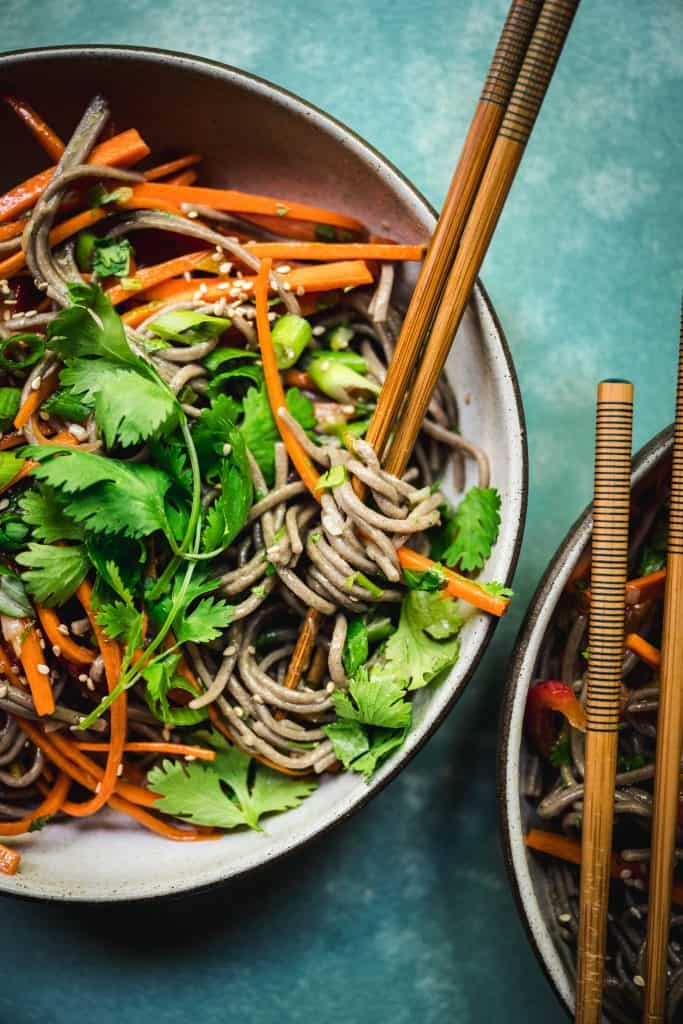 overhead of japanese soba noodle salad in a bowl with chopsticks