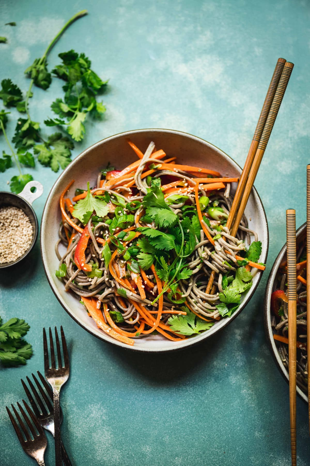 overhead of japanese soba noodle salad with citrus scallion dressing on a teal background