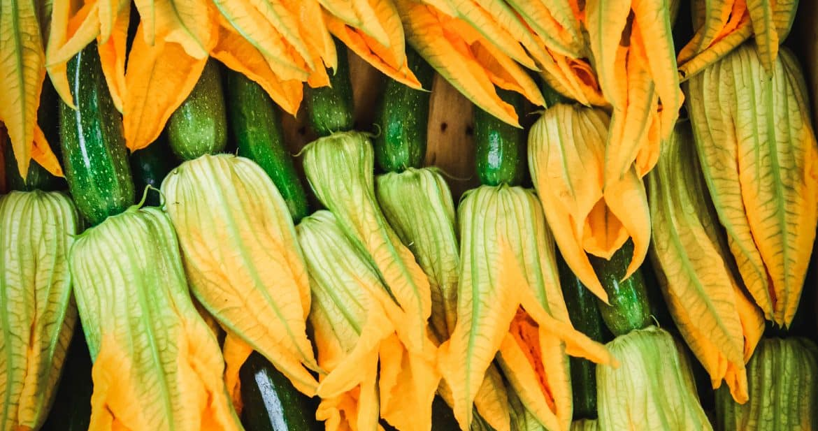 Overhead view of squash blossoms in bin at farmers market